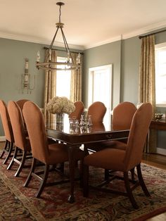 Currey And Company Toulouse Chandelier and Aidan Gray candle sconce are the perfect pair for this orange and sage dining room.  So pretty!