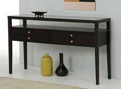 This brown console table makes a nice addition to an entryway, family room, or bedroom. The lovely Halifax-finished rubberwood frame and glass top creates elegance and durability, and two spacious drawers provide storage and organization.