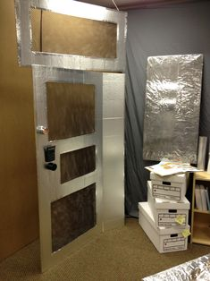 The Big Idea: The cage-like door with digital passcode entrance will help set the scene that this is a secure room with important contents. Supplies Needed: Foil covered 4 x 8 foot insulation foam board (Home Improvement Stores), yardstick, utility knife, netting fabric, aluminum tape, medium size black calculator, black and silver aerosol can lids.…