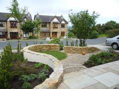jardinet devant la maison aménagé avec des plantes vivaces et décoré de gravier et d'une clôture basse en pierre naturelle