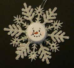 Snowflake with a pop bottle cap painted face.