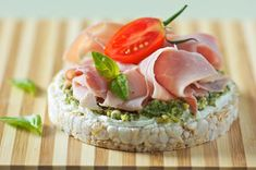 Spread cream cheese onto a Kallo sea salt and balsamic vinegar rice cake and top with fresh green pesto and ham. Garnish with tomato and salad leaves.