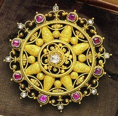 A gold, ruby and diamond Etruscan revival brooch, circa 1860 The circular-shaped openwork panel centrally-set with a raised rose-cut diamond within gold borders of ropetwist, filigree, bead and granulation decoration, the outer border composed of old-cut diamond ropetwist finials with alternating cushion-shaped rubies