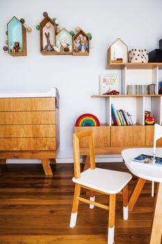 Dormitorio de un bebé en un departamento de Palermo con pisos y muebles nórdicos (Krethaus) de madera. En la pared, estantes con forma de casitas contienen juguetes.