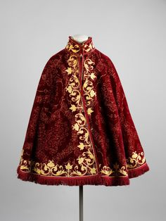Man's Cloak 1560-1569 The Victoria & Albert Museum Spain This example is made of Italian silk with a red pile in a palmate pattern on a voided cream satin ground. It was probably crafted from another garment, possibly a petticoat. The collar, front and hem of the cloak have been decorated with applied yellow satin outlined with silk cords, in a scrolling design of stylised foliage.