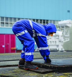 WATERPROOF OVERALL WITH REFLECTIVE TAPES Model: 104/R The overall is fastened with hidden zip under a storm flap with a hood, sleeves and legs with windstoppers. It  has reflective tapes on body, sleeves and legs to make workers more visible during the work. The product is made of PVC/polyester fabric, called Plavitex. Thanks to double welded high frequency seams the product protects against rain and wind.
