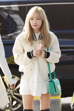 i really like the contrast between her really girly dress and the varsity jacket plus those thigh high boots? = perfection