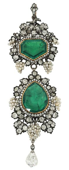 A LATE 19TH/EARLY 20TH CENTURY EMERALD AND DIAMOND BROOCH PENDANT. The surmount with fancy-cut emerald and single-cut diamond cluster centre, to a fruiting vine surround, composed of bunches of seed pearl grapes among old-cut diamond-set vine leaves, suspending a pear shaped emerald drop with similarly-set seed pearl and diamond border, to a further briolette-cut diamond terminal, mounted in silver and gold. #Victorian #Edwardian #brooch #antique