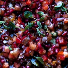 Yotam Ottolenghi's vegan Tomato and pomegranate salad is packed with a rainbow of flavour - great for using up a glut of tomatoes!