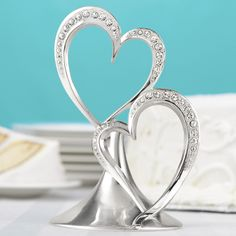 This silver-plated cake topper celebrates that special day with a double heart design and sparkling faux rhinestone accents.