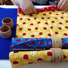 Rolling cloth napkins and using a napkin ring. Montessori Practical Life exercise.