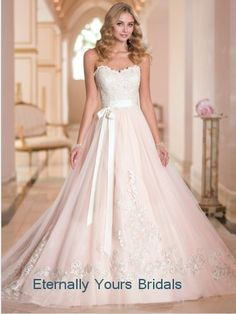 Add a bit of glamorous charm to your big day with this designer wedding dress in Tulle and Lace . Designer details include scalloped Lace edging along the neckline, Lace appliques throughout the fitted bodice and a full, flowy Tulle skirt with Lace vines and a court train.   Pictured in Pink an...
