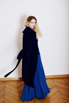The COZY NAVY is a classic style oversize coat. It is made form a saturated, dark blue coloured, plushy fabric. The coat has a soft lining on the inside. It has no closing at the front, but it comes with a waistband in the same fabric. Or it can be worn with a belt.