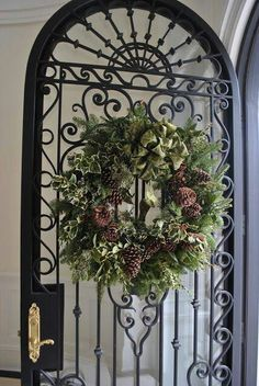 Not sure what I love the most...the iron door or the wreath!  #Christmas #greenery #wreath
