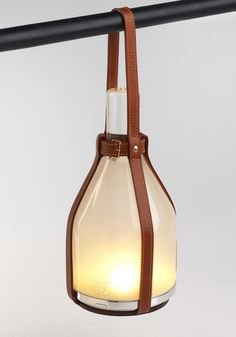 'Bell-Lamp' by London-basedEdward Barber and Jay OsgerbyofBarber Osgerby. Thlampfeatures LED lights and a handcrafted Murano-glass frosted enclosure. Cordless, solar powered, with a removable leather strap, the piece offers a perfect on-the-go illumination. Available made to order for $3,350.