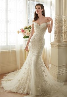Off-the-shoulder misty tulle over allover lace trumpet wedding gown with…
