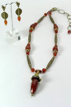 """#30312 Faceted carnelian and bronze drop on carnelian and bronze tubes. Bronze clasp and 5"""" extender chain."""