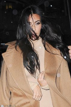 Keeping cosy: Kim looked rather shocked as she wrapped up in a camel wool coat to brave the New York rain earlier in the evening