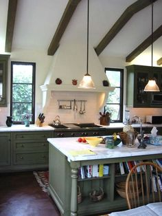 Kitchen - Spanish Revival style 3 light casement windows flank the plaster vent hood. Beam ceilings, marble counters, tile walls.