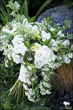 A mixed summery wedding bouquet of white majolica roses, mint, spirea, yellow roses, cedar, white peonies and white freesia.  Photo by www.orchardcovephotography.com