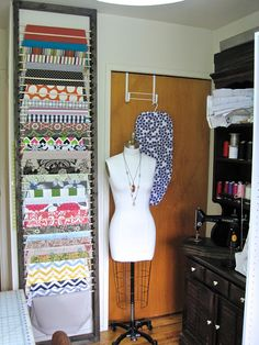 The Project Lady: Fabric Organizer - Wood Frame with Slots for Dowels!  Great way to hang fabric.  (She originally slipped the dowels through loops on straps of fabric and hung on the door, but the fabric weight was pulling the door off the hinges.)