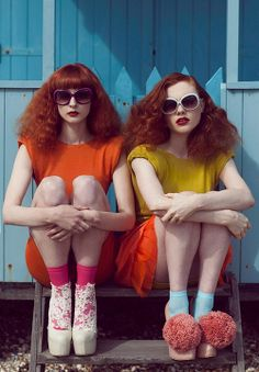 two young women sitting on steps with sunglasses and bright dresses