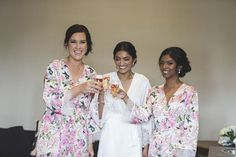 Bridal party getting ready in their Homebodii bridesmaid and Bridal robes before the wedding. Bridesmaids are wearing Homebodii Floral Zariah Robes. Bride is wearing our Lola White Matte Satin Kimono Robe embroidered with Mrs Wright and their wedding date. #embroideredbridalrobe