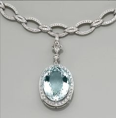 An aquamarine, diamond and eighteen karat white gold pendant-enhancer and necklace  the pendant-enhancer centering an oval-shaped aquamarine within a surround of round brilliant-cut diamonds, suspending from a necklace designed as openwork cartouche and navette-shaped links, set throughout with round brilliant-cut diamonds; estimated aquamarine weight: 33.45 carats; estimated total diamond weight: 7.10 carats; length: 15in.