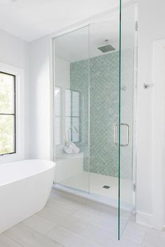 An oval freestanding bathtub sits on a light gray wood like floor beneath a window and faces seamless glass shower boasting a marble bench and seafood green fish scale pattern wall tiles fixed over a white floor Grey Bathrooms, Modern Bathroom, Small Bathroom, Bathroom Ideas, Bathroom Showers, Master Bathrooms, Glass Tile Bathroom, Bathroom Organization, Glass Showers