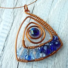 Pro královnu Vytvořeno z tepaného lakovaného měděného drátu 1 mm, vypleteno skleněnými korálky (broušené,hladké, rokail) vše v odstínech královské modré. Zavěšeno na bižuterním lanku měděné barvy dlouhém cca 40 cm, zapínání na karabinku. Velikost šperku je 4x4,5 cm.