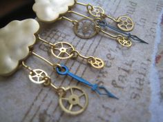 It's Raining Time! Antique watch parts have been added to brushed golden clouds to create a whimsical rain.