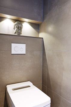 Stylish toilet / cloakroom area. Recessed lighting and large format floor to ceiling tiles look elegant while the wall mounted toilet with concealed cistern gives this design a minimal and luxurious look.  SOUTH DEVON I Sapphire Spaces | Sapphire Spaces - Image Alt