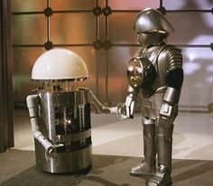 Twiki (voiced by Mel Blank of Looney Tunes fame) and Dr. Theopolis around his neck, holding hands with a cleaning droid - 'Buck Rogers in the 25th Century' (1979–1981)