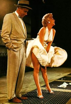 The Seven Year Itch (1955). Tom Ewell watching Marilyn Monroe do her subway grate magic at Lexington & 51st Street in New York City. A huge crowd formed, and they cheered every time the dress flew up. Standing across the street was Marilyn's husband, baseball great Joe DiMaggio. The marriage was strained for many reasons, not the least of which was the fact that Marilyn was an exhibitionist and Joe was a very private man. This was the last straw for Joe.