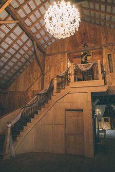 A beautiful barn wedding venue featuring an elaborate chandeliere and rustic decor. | Rivercrest Farm in Ohio