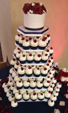 - Navy Blue, Burgundy & Ivory cupcake tower with handmade gum paste rosettes and sugar pearls on each cupcake. Cake topper is covered in ivory fondant with swiss dots topped with handmade gum paste burgundy roses, ivory hydrangeas and filler flowers.  Stand was custom made by my wonderful boyfriend!