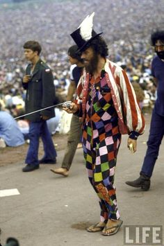 Paul Foster, wearing a top hat w. wings, a multi-colored outfit, & a red & white striped jacket, walking during the Woodstock Music & Art Festival. 1969 Woodstock, Festival Woodstock, Woodstock Hippies, Woodstock Music, Recital, Beatles, Joe Cocker, Hippie Love, Hippie Art