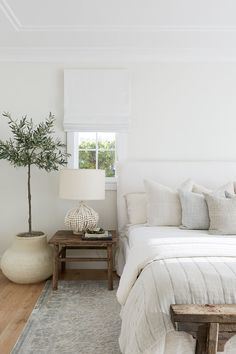 White slipcovered headboard bed features a linen bedding and linen pillows besid. - White slipcovered headboard bed features a linen bedding and linen pillows beside a potted olive tr - Slipcovered Headboard, Cream Headboard, Linen Headboard, Modern Headboard, Headboards, Interior Modern, Simple Interior, Modern Exterior, Interior S