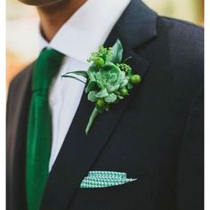 Groom has a DEEP emerald suite for the wedding and groomsmen have black with a green boutonnière
