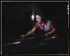 Metal parts are placed on masonite by this woman employee before they slide under the multi-ton hydropress, North American Aviation, Inc., Inglewood, Calif.