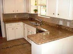 Brown granite and cream cabinets. Neutral backsplash.