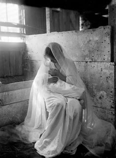 """Historical black and white photograph of an image originally titled """"The Manger"""" showing a young mother in a white gown with a white lace veil, holding her baby in her arms while seated in a manger, bright sunlight shining in from the window behind her, Newport, Rhode Island, 1901"""