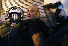A protester bleeds as he is arrested by riot police following clashes in Athens, Greece July 15, 2015. REUTERS/Yannis Behrakis