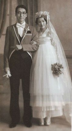 Vintage Korean newlyweds, the bride in a hanbok style dress (I can't find a date for this but elements like the groom's accessories, the photo quality, pose & background, and the overall silhouette of the bride makes me think 1920s-30s)
