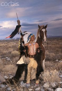 Shoshone Elder Wearing Bison Robe:Shoshone-Bannock elder dressed in traditional historic clothing, including leather leggings, loin cloth and eagle feather headdress, stands wrapped in a buffalo hide robe by his horse on a typical Great Basin landscape. Marilyn Angel Wynn photography
