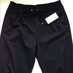 Michael Kors Black Pants: NWT NEW with tags. Pencil leg pants, that are loose and comfy. Elastic for the waist and the ankles. Gold embellishments. Pockets on back and front. Super Classy for work or you can dress them down. Tag has marking on it indicating the sale price from store (66.99). MICHAEL Michael Kors Pants Ankle & Cropped