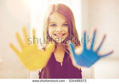 education, creation, art, people and children concept - happy girl showing painted hand palms at home