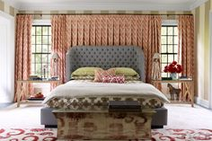 The bed and side tables in the master bedroom are by Thom Filicia, the hammered metal bench is by Paul Mathieu, and the curtains are of a linen from Jerry Pair.