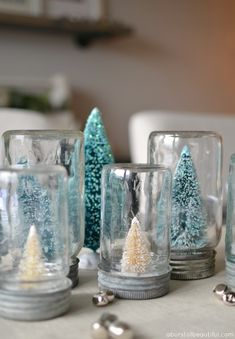Homemade bottle brush tree snow globes add a whimsical touch to this farmhouse table.