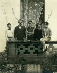 Black and white photo of Frida kahlo standing on a balcony with her sister Christina and friends.  Frida is in the middle.  Coyoacán, Mexico 1926